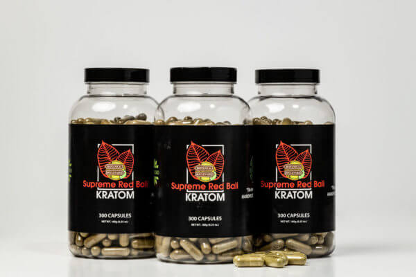 supreme red bali kratom capsules on tabletop